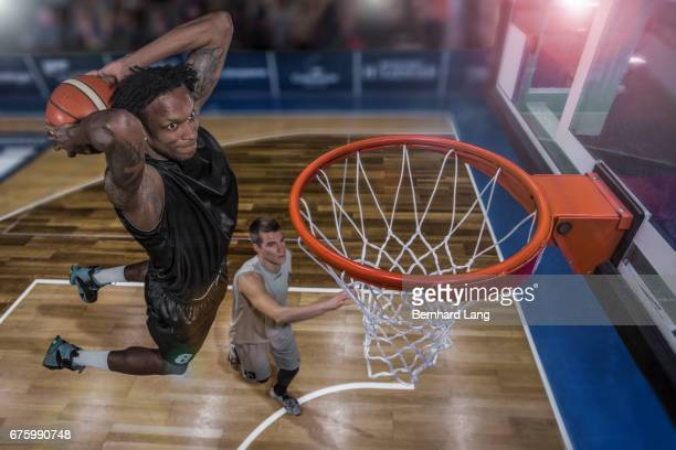 Basketball player jumping to dunk ball in arena