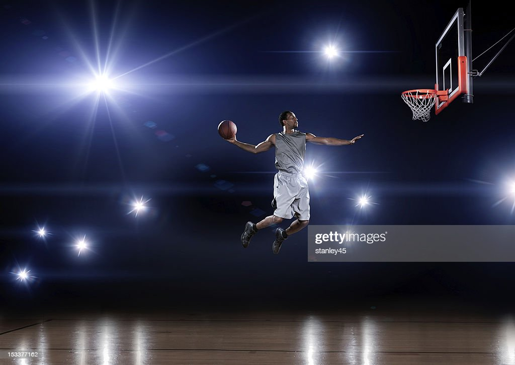 Basketball player jumping toward the net : Stock Photo