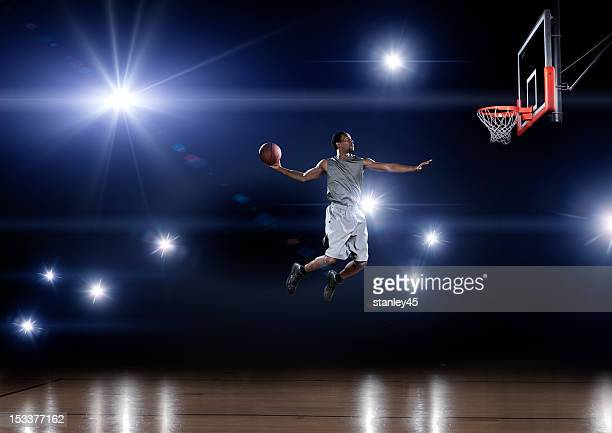 Basketball player jumping toward the net