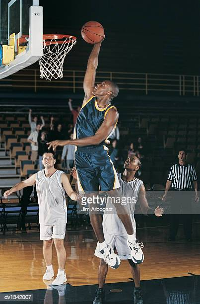 basketball player jumping towards the hoop holding the ball in his hands - female umpire stockfoto's en -beelden