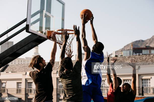 Basketball player jumping with ball in both hands and about to score a point