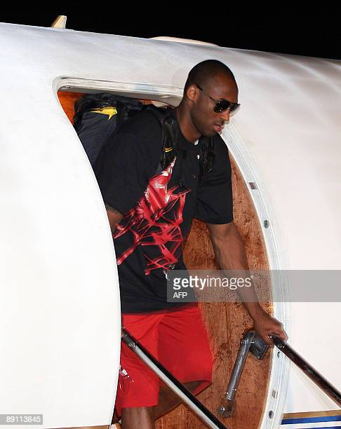 Basketball player Kobe Bryant of the Los Angeles Lakers disembarks from a plane shortly after arriving at the Manila international airport on July 20...