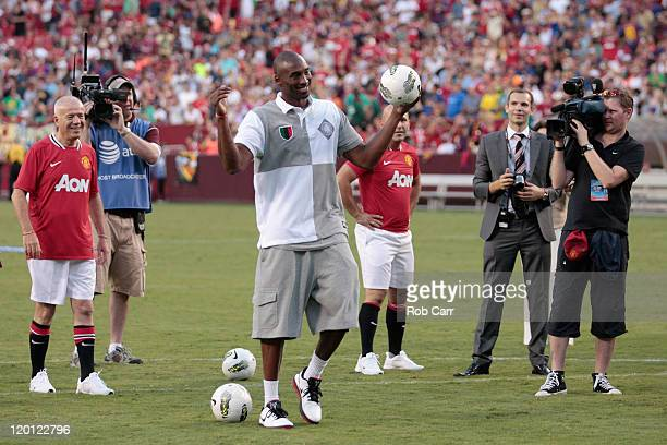 Basketball player Kobe Bryant reacts to the crowd during a half time event at the Manchester United and Barcelona friendly match at FedExField on...
