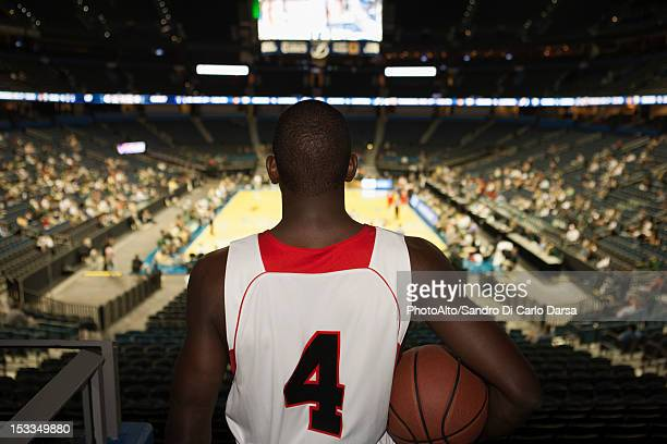 basketball player looking down at stadium, rear view - basketball stadium stock photos and pictures