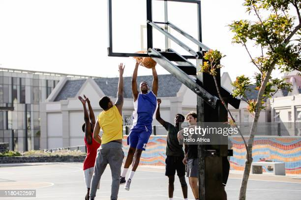 Basketball player makes a hoop and hangs on