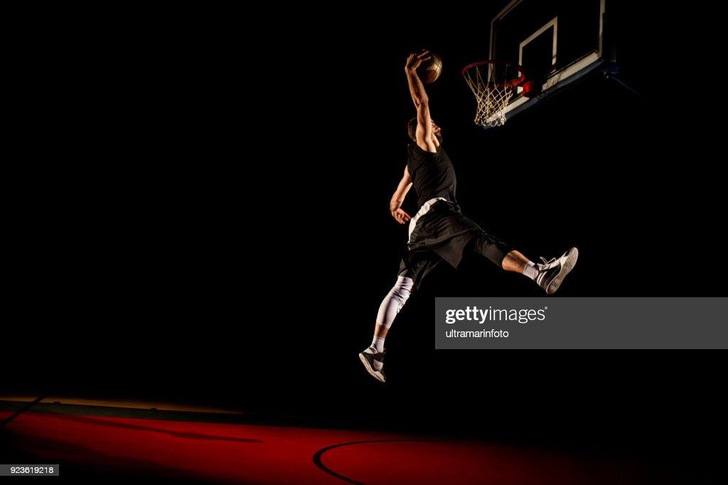 Basketball player makes slam dunk - Man Dunking : Stock Photo
