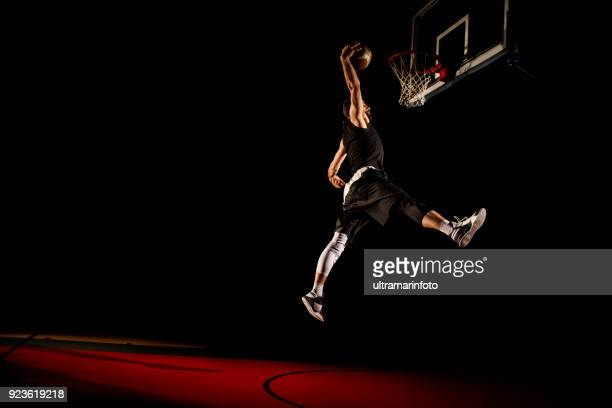 basketball player makes slam dunk - man dunking - slam dunk stock pictures, royalty-free photos & images