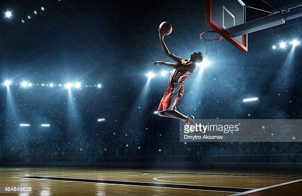 basketball player makes slam dunk - basket stock photos and pictures