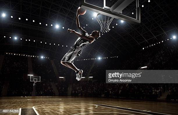 basketball player makes slam dunk - basketball stadium stock photos and pictures