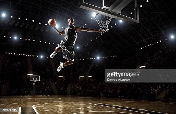 basketball player makes slam dunk - shooting baskets stock photos and pictures