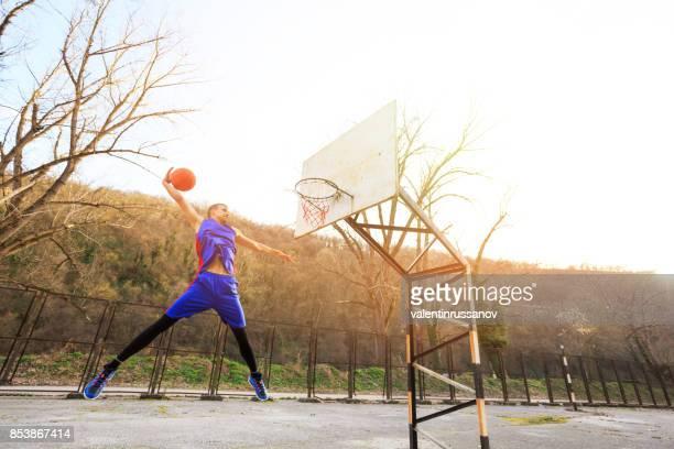 屋外のコートでスラムダンクを作るのバスケット ボール選手