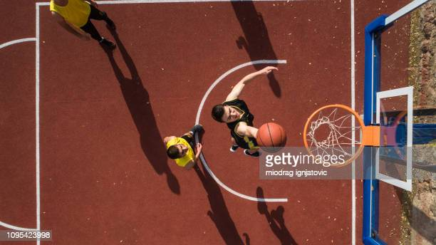 basketbal speler maken slam dunk - basketbal teamsport stockfoto's en -beelden