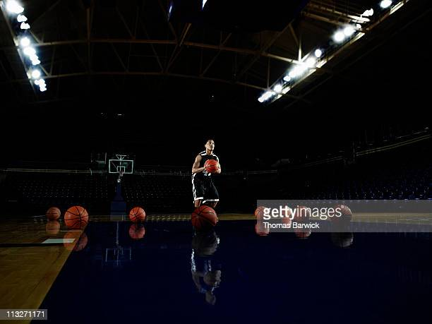 Basketball player practicing free throws in arena