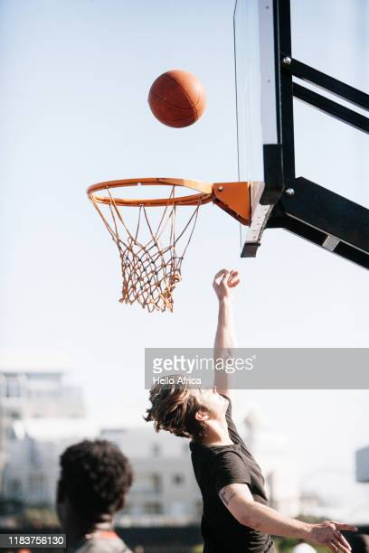 A basketball player reaches up as a ball makes it way to the hoop