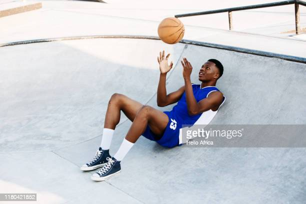 Basketball player relaxing in a skating bowl throwing a ball in the air