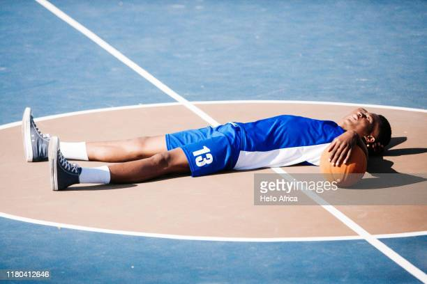 Basketball player resting in middle of basketball court
