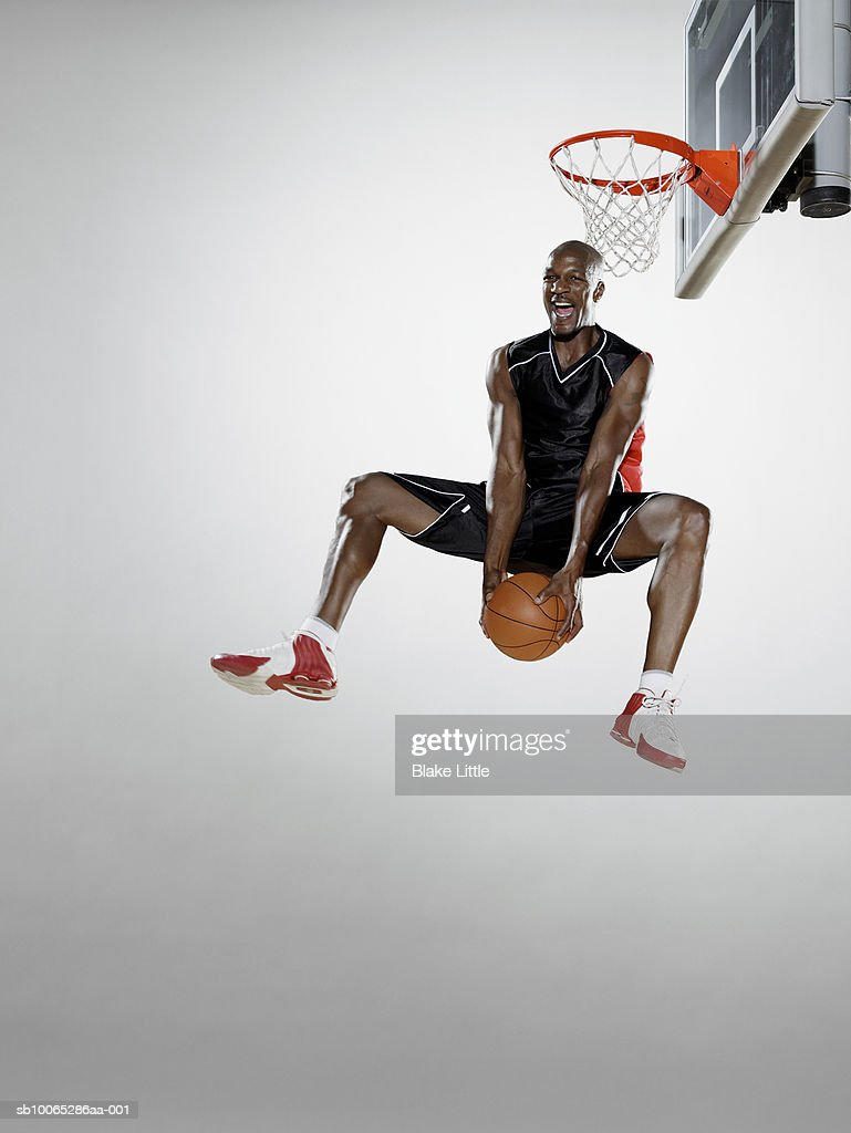 Basketball player reverse dunking basketball, low angle view : Foto stock