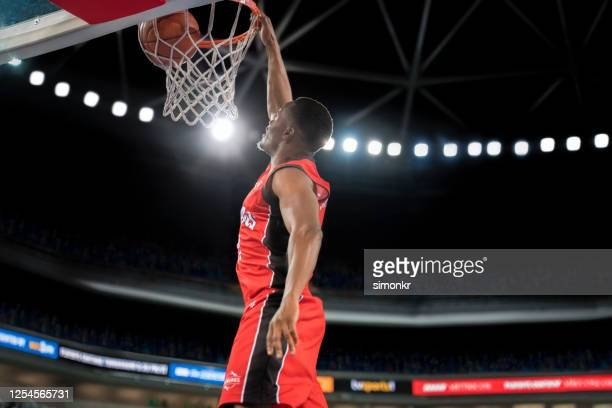 basketball player scoring slam dunk - basketball player stock pictures, royalty-free photos & images