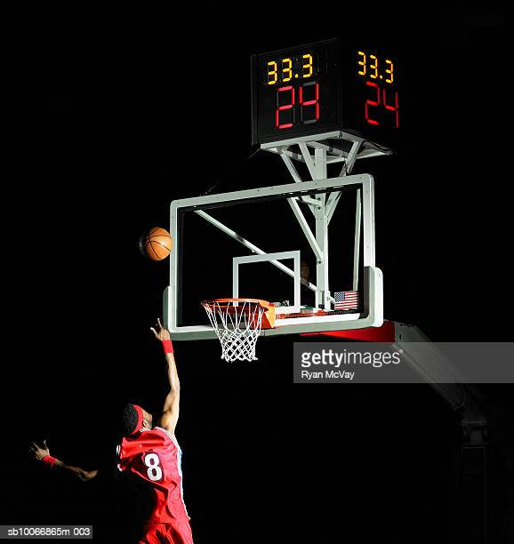 Basketball player shooting basketball in to hoop, rear view