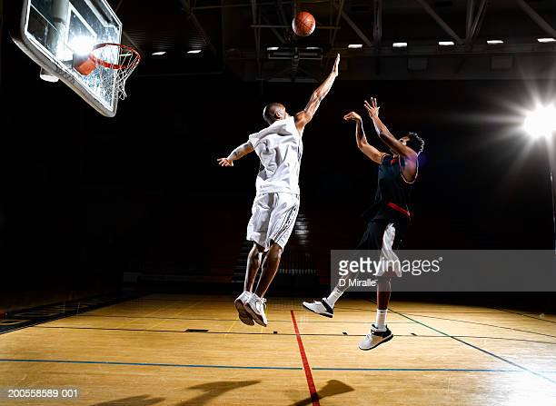 basketball player shooting fade away while opponent blocks shot - shooting baskets stock photos and pictures
