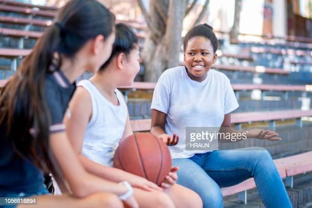 jugador de baloncesto encogiéndose por amigos en el campus - encogerse de hombros fotografías e imágenes de stock