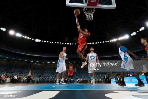 de speler van het basketbal slam dunking bal - sportwedstrijd stockfoto's en -beelden