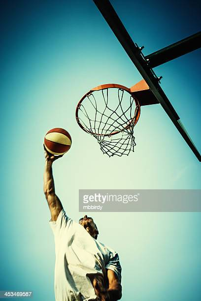 basketball player slam dunking ball - slam dunk stock pictures, royalty-free photos & images