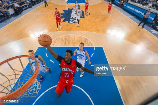 basketball player slam dunking basketball - basketball player stock pictures, royalty-free photos & images