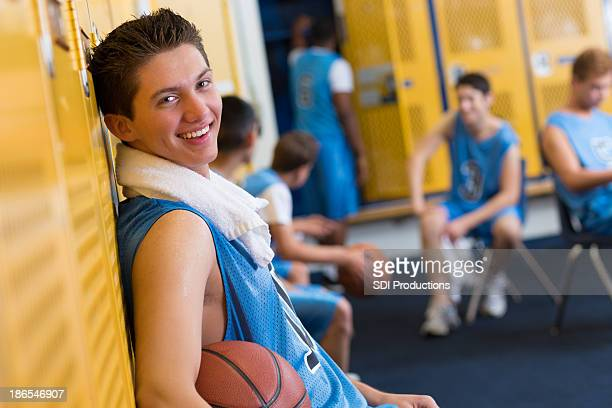 Basketball player smiles in locker room after game