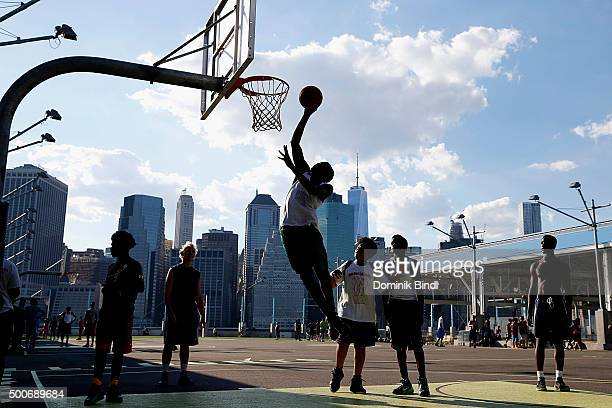 A basketball player soars through the air toward the hoop trying to score during a pickup game on an outside court on Pier 2 in Brooklyn Bridge Park...