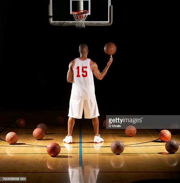 Basketball player spinning ball on fingertip, rear view