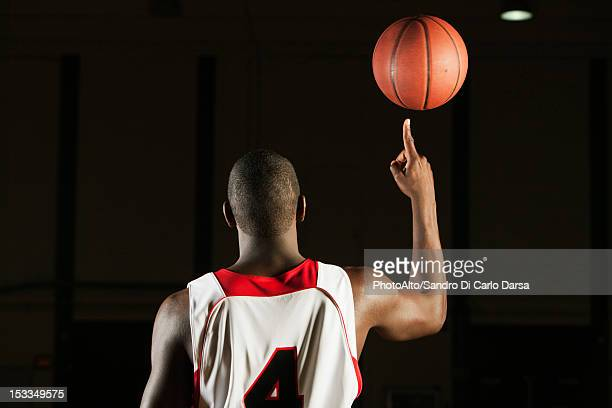 Basketball player spinning basketball atop finger, rear view