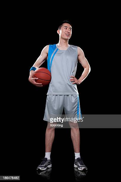 basketball player standing, black background - バスケットボールのユニフォーム ストックフォトと画像