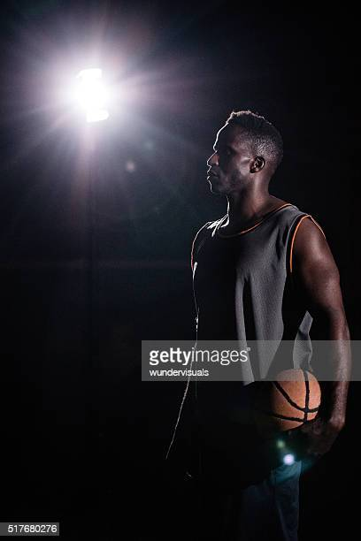 Basketball Player Standing Facing Left and Holding Ball in Night