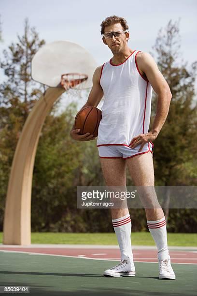 Basketball player standing on court holding basketball