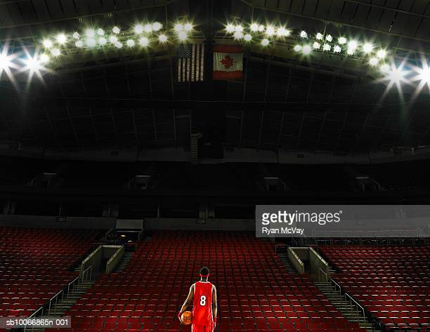 basketball player standing on court holding basketball, rear view - basketball stadium stock pictures, royalty-free photos & images