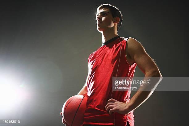 Basketball player standing with ball