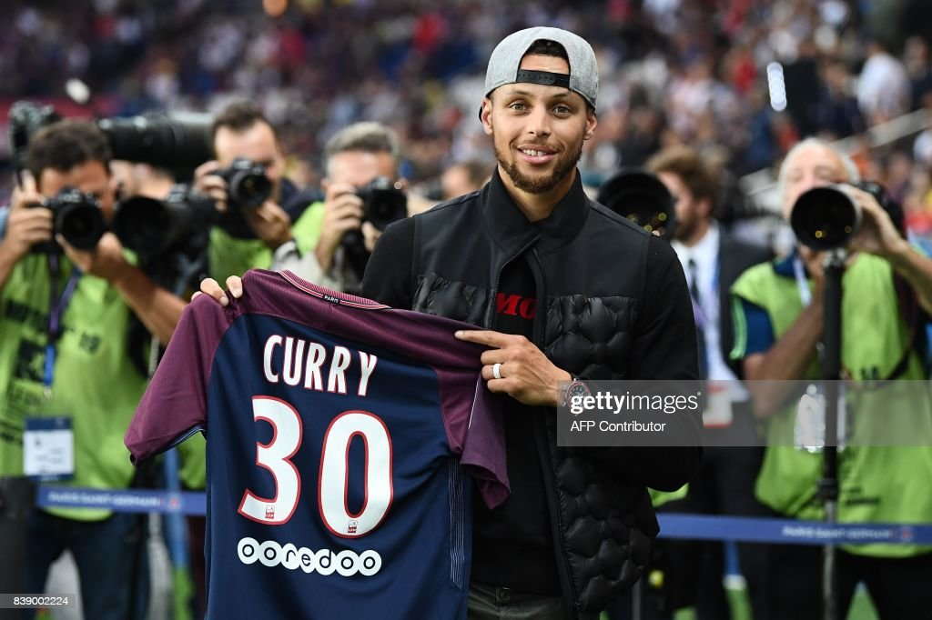 US basketball player Stephen Curry poses with a PSG jersey prior to the French L1 football match between Paris Saint-Germain (PSG) and Saint-Etienne (ASSE) on August 25, 2017, at the Parc des Princes stadium in Paris. /