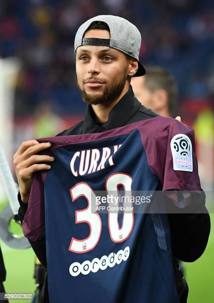 US basketball player Stephen Curry poses with a PSG jersey prior to the French L1 football match between Paris SaintGermain and SaintEtienne on...