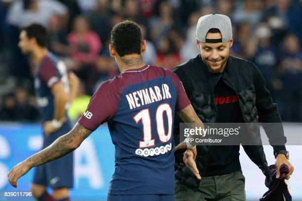 TOPSHOT US basketball player Stephen Curry taps hands with Paris SaintGermain's Brazilian forward Neymar at the start of the French L1 football match...