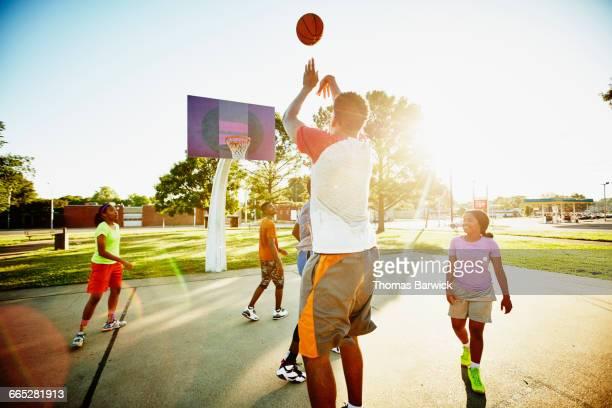 Basketball player taking shot over defender