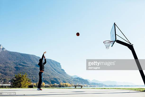 Basketball player throwing ball toward hoop