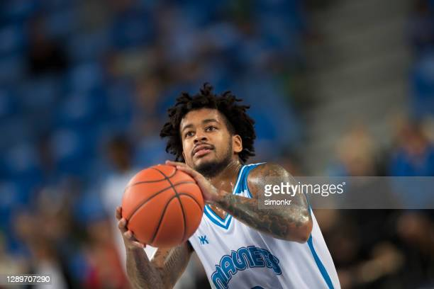 basketball player throwing basketball - basketball uniform stock pictures, royalty-free photos & images