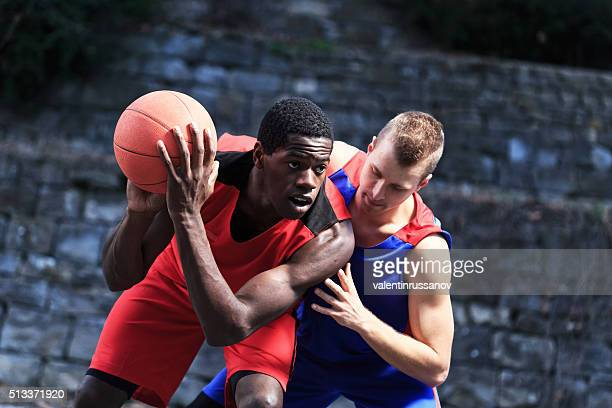Basketball Player try to shoots against defender - black background