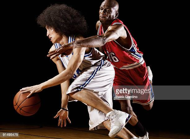 basketball player trying to take basketball from opponent - ドリブル ストックフォトと画像