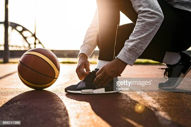 basketball player tying shoelace - basketball shoe stock photos and pictures