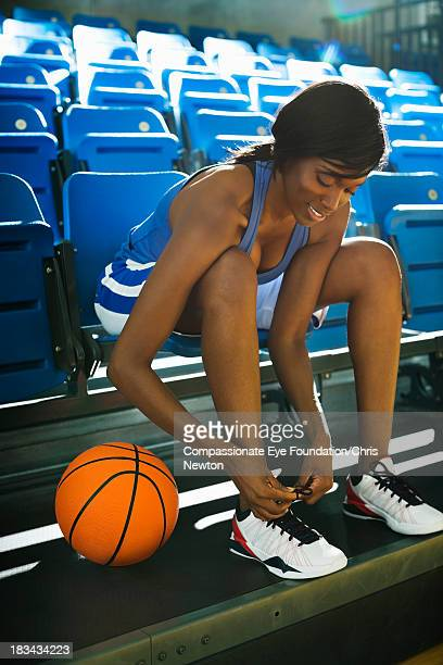 Basketball player tying shoes in gym