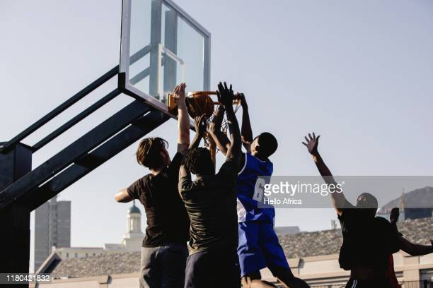 Basketball player wearing number six hanging on hoop after scoring