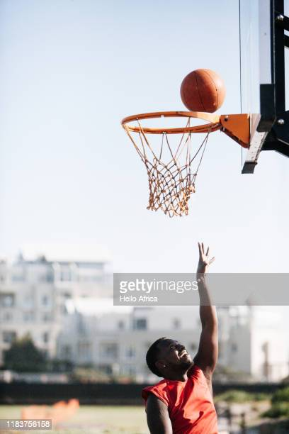 Basketball player wearing red throwing the ball up to score