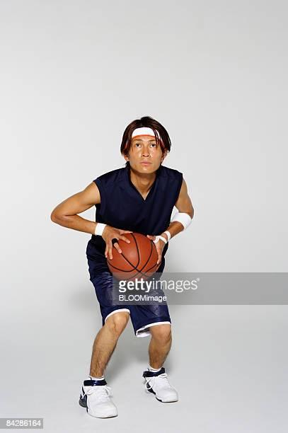 Basketball player with ball, studio shot